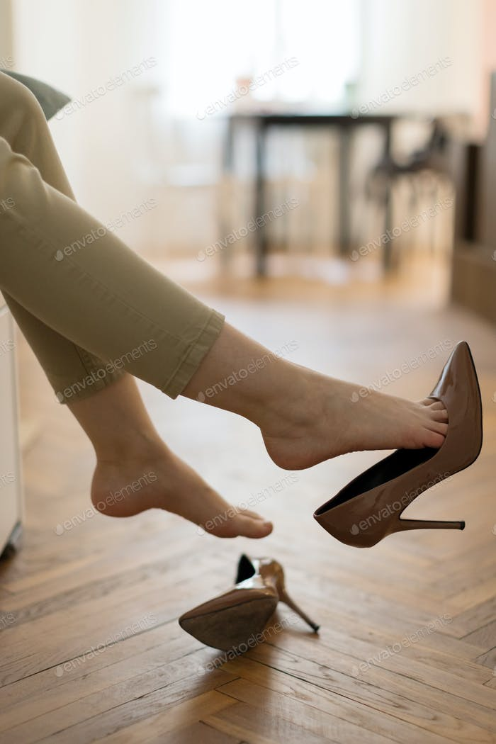 Cropped image of tired woman take off high heels shoes sit barefoot in living room with no footwear