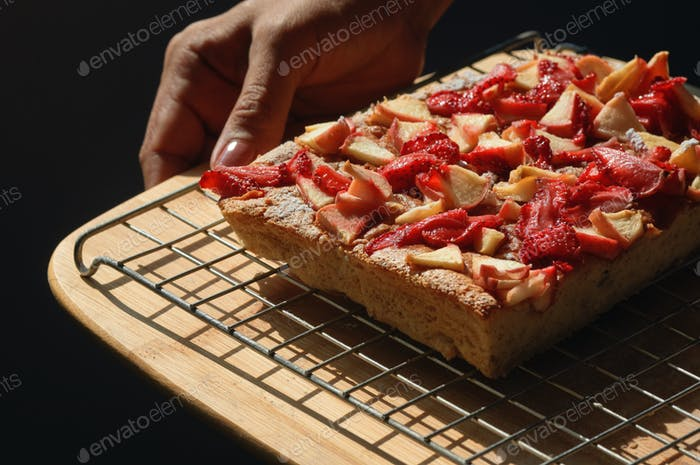 Baker holding the fruit cake on cooling rack
