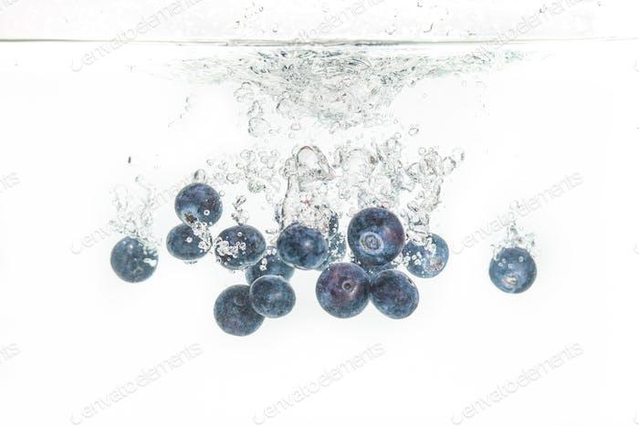 Heidelbeeren sinken unter Wasser mit Luftblasen isoliert auf weißem Hintergrund