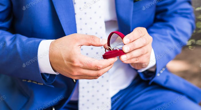 Man's hand holding engagement ring