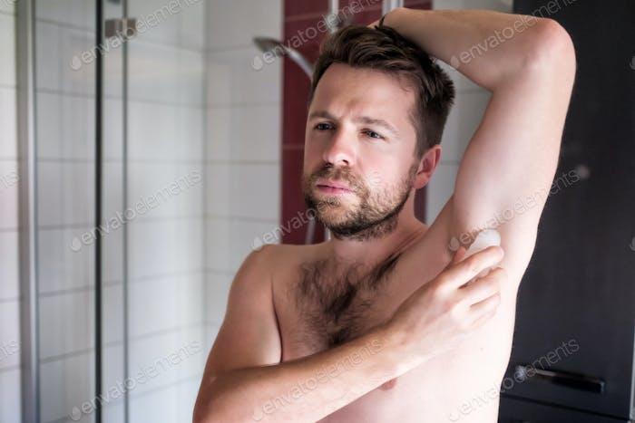 shirtless kaukasischen Mann setzen Deodorant in die Bad