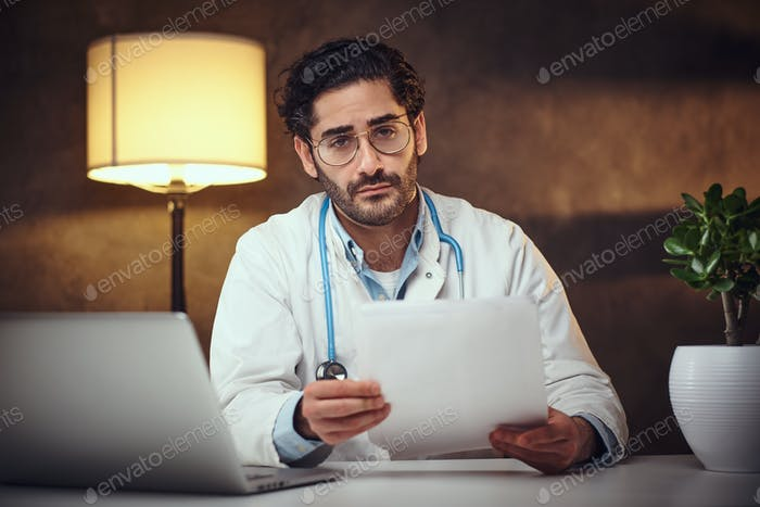 Busy doctor in his office is working with paperworks