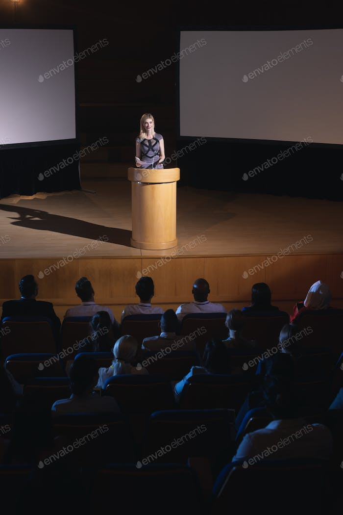 Blonde Caucasian businesswoman standing around podium and giving presentation to the audience