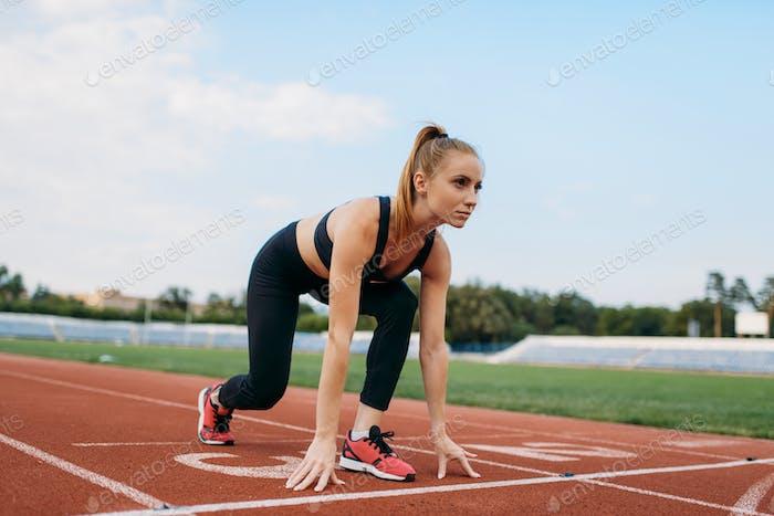 Female runner on start line, training on stadium