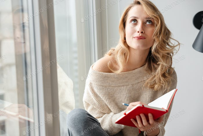 Woman indoors at home writing notes