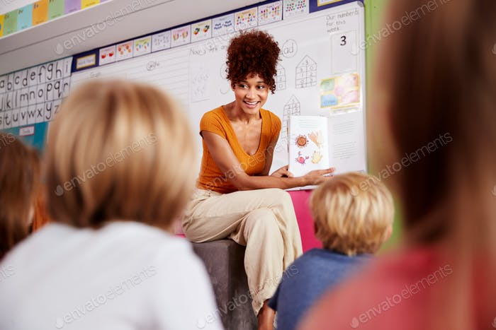 Female Teacher Reading Story To Group Of Elementary Pupils In School Classroom