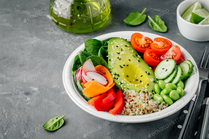 Buddha bowl with Avocado, quinoa, tomatoes, cucumbers, spinach, carrots, paprika and edamame