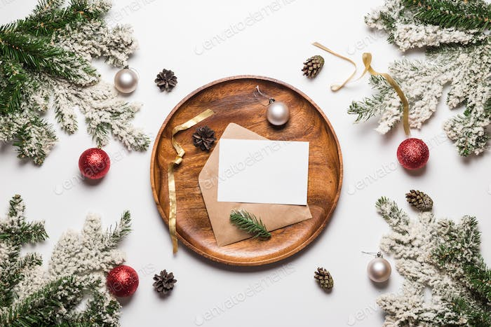 Christmas and new year invitation in envelope on wooden dish with christmas decoration