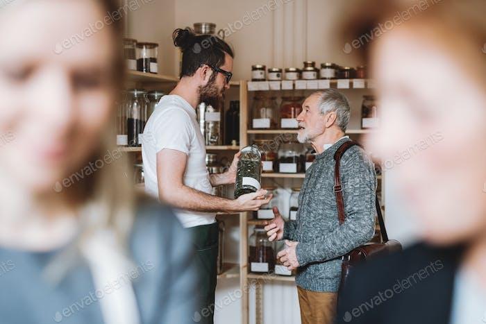 Young shop assistant serving a senior man in a zero waste shop.