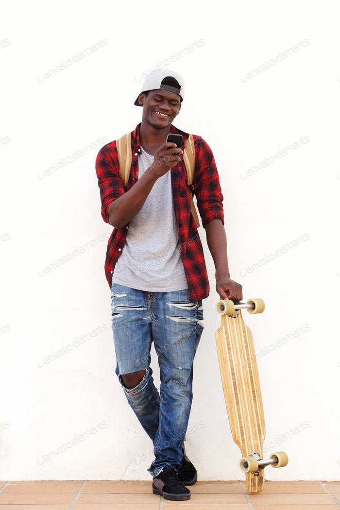 Smiling African American guy standing with skateboard and mobile phone