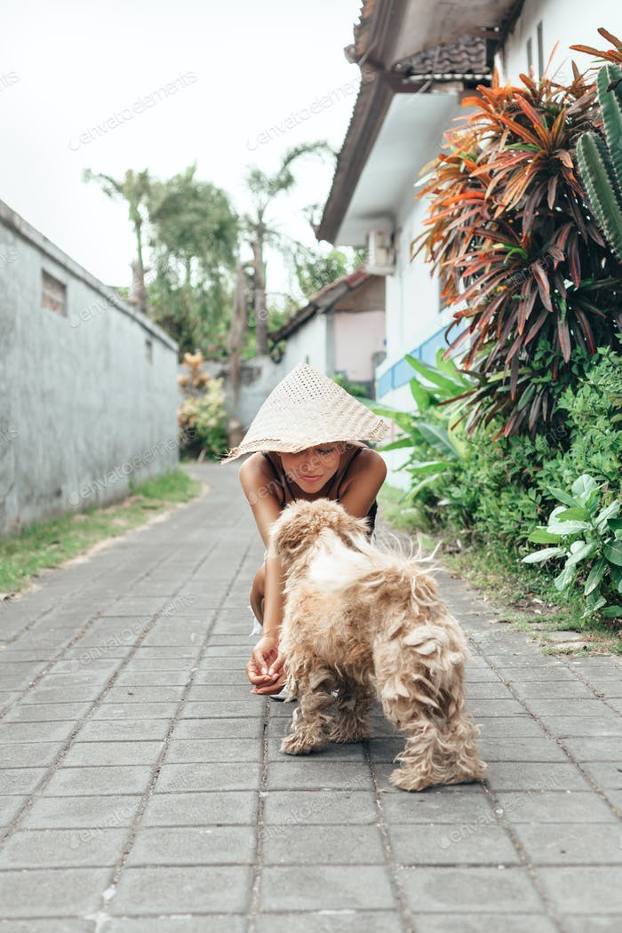 Young woman with dog playing on road