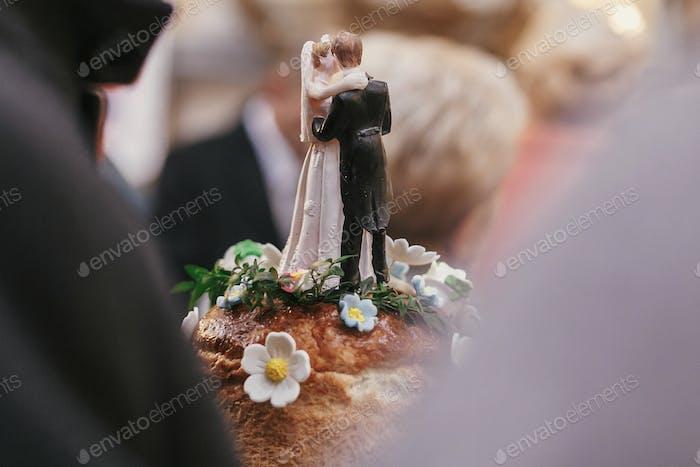 wedding cake topper. bride and groom figurines on top of wedding cake
