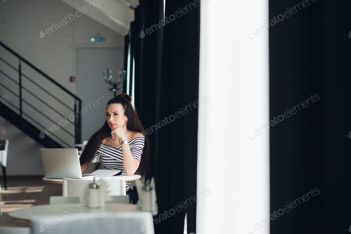 Looking for inspiration. Young beautiful pensive woman making some notes and looking away while