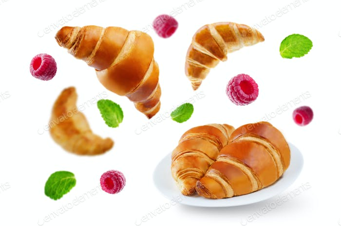 Flying croissants with raspberries and mint leaves isolated