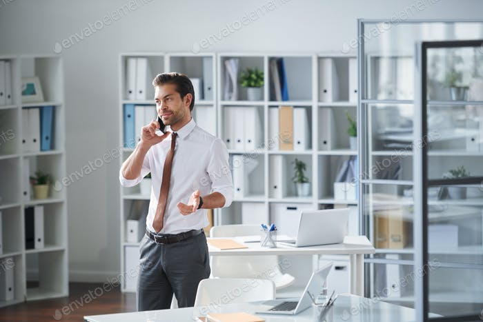 Young lawyer in formalwear consulting client by phone