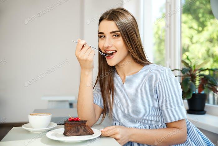 Junge attraktive kaukasische Dame genießen Schokoladenkuchen mit heißem Kaffee im modernen Café im