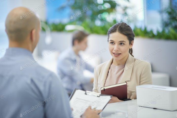 Lächelnde Frau im Gespräch mit Manager bei der Arbeit