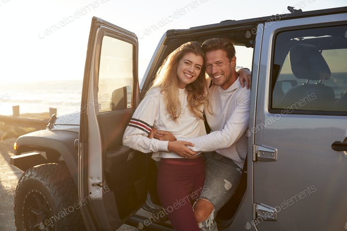 Young white couple on a road trip embracing by their car