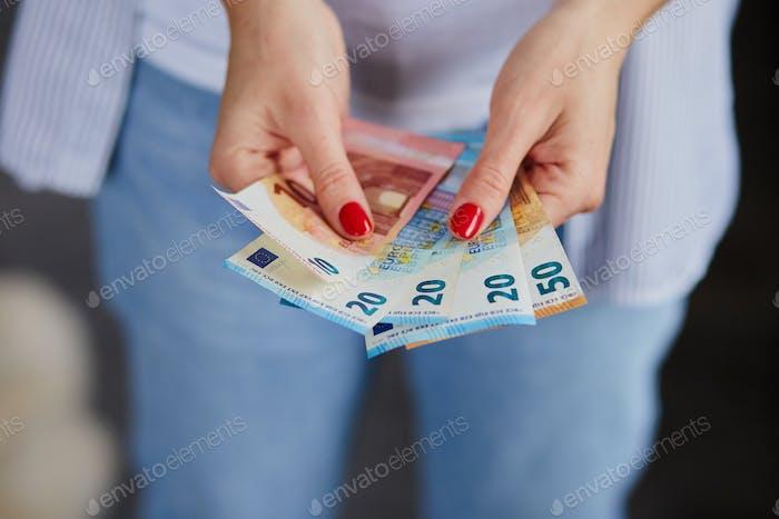 Eine Frau hält Eurogeld in ihren Händen.