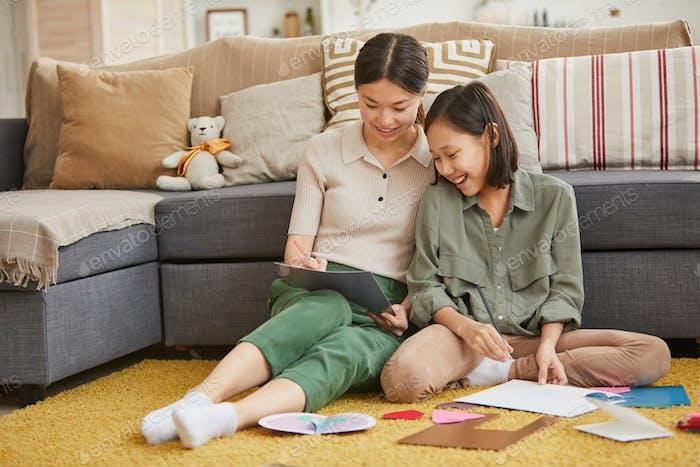 Mädchen auf Boden tun Papier Handwerk