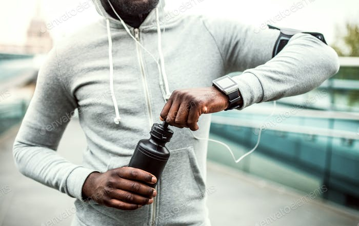 A close-up of young sporty black man runner with water bottle in a city.
