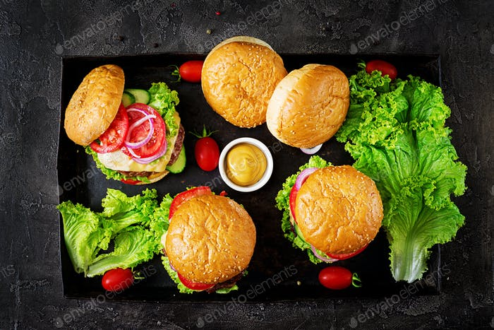 Hamburger with beef meat burger and fresh vegetables on dark background. Tasty food. Top view