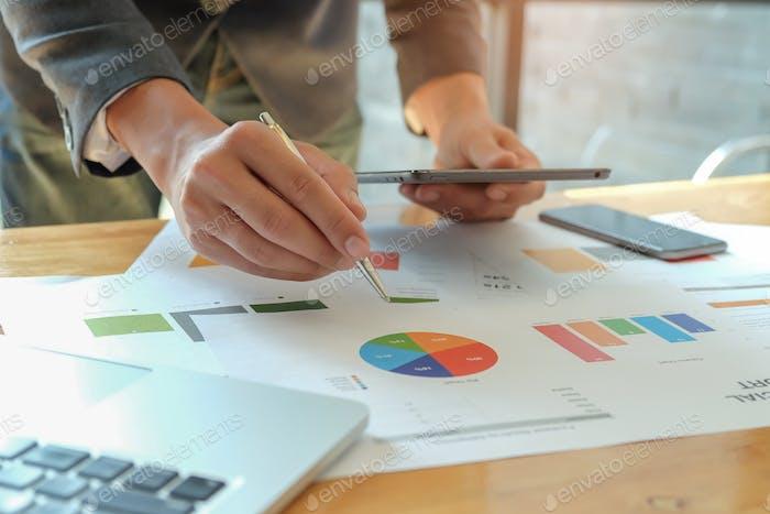 Man Hand hält Stift zeigt auf DeskมBusiness-Konzepte zu graphieren.