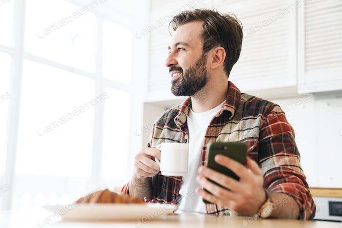 Retrato de sonriente hombre barbudo usando celular y beber café