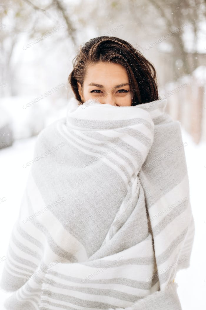 Charming dark-haired girl wrapped in a gray scarf is standing in a snowy street on a winter day