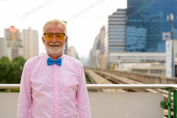 Handsome senior tourist man exploring the city of Bangkok, Thail