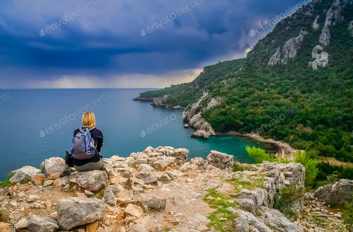 Female trekker resting on a cliff in Olympos