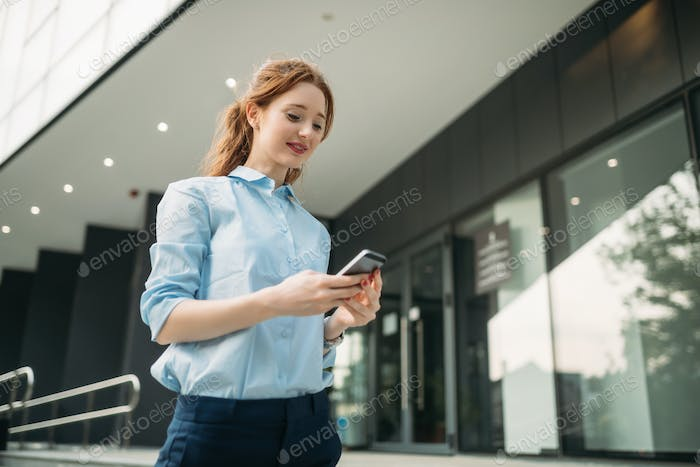 Attractive young businesswoman using mobile phone outside