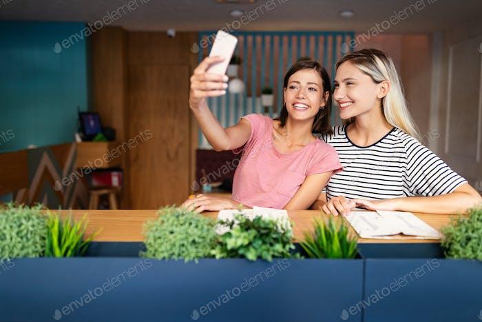 Happy smiling women friends having fun and taking selfie