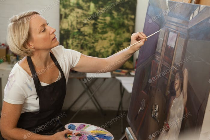 Attentive woman painting on canvas