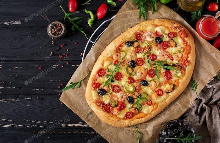 Köstliche Meeresfrüchte Garnelen und Muscheln Pizza auf einem schwarzen Holztisch. Italienisches Essen. Ansicht von oben