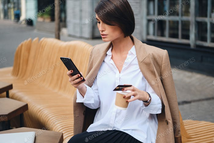 Attractive businesswoman with credit card confidently using cellphone during lunch in cafe on street