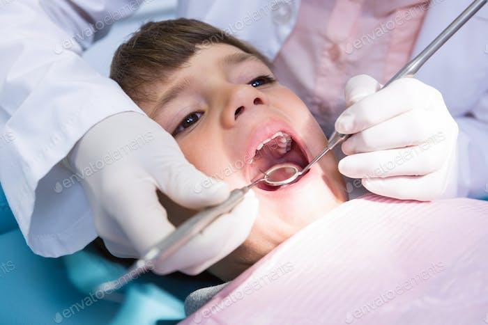 Dentist examining boy mouth at medical clinic