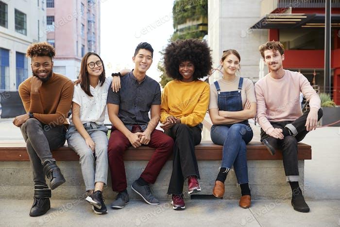 Sechs junge erwachsene Freunde sitzen in einer Reihe auf einer Bank in einer Stadtstraße lächelnd Kamera, volle Länge