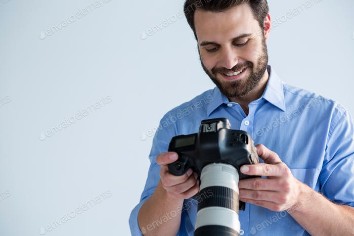 Male photographer reviewing captured photos in her digital camera