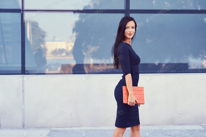Brunette business woman dressed in a black formal clothes and high heels against of a skyscrapers.