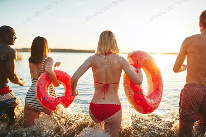 Carefree friends in swimwear running into a lake at sunset