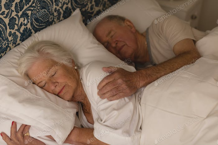 Senior couple sleeping together in bedroom