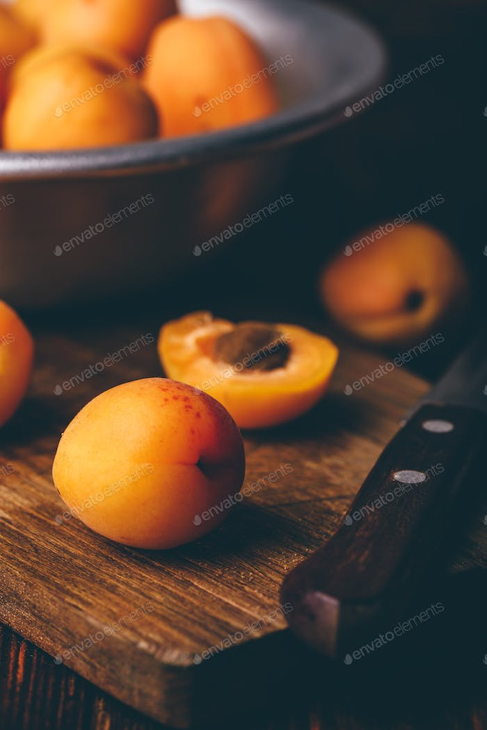 Mellow apricots with knife over cutting board