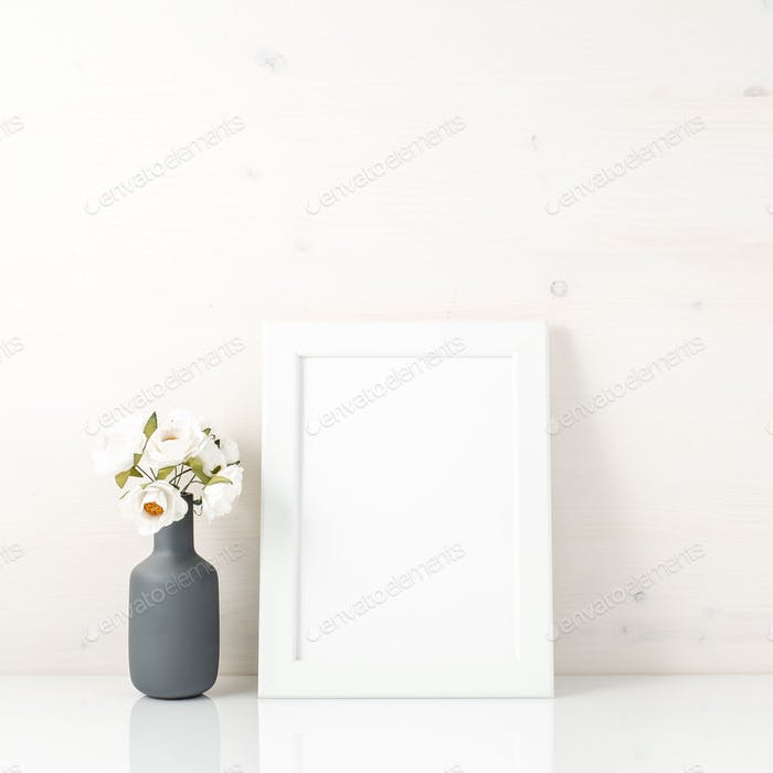 Blank white frame, flower in vaze on a white table against white wall with copy space. Mock up.