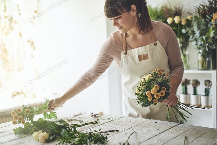 Young woman making a floral arrangement in her flower shop