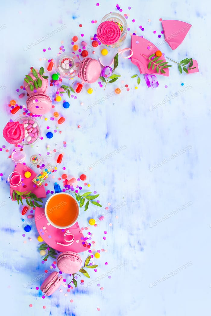 Colorful celebration flat lay with party supplies, confetti and sweets. Pink macarons with tea cup