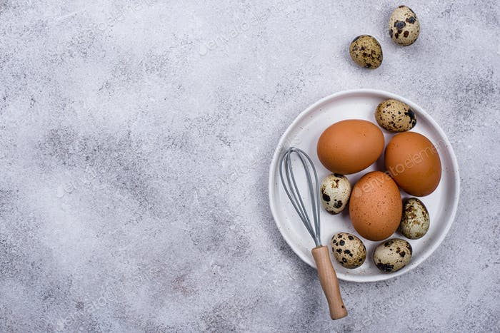Chicken and quail eggs with whisk