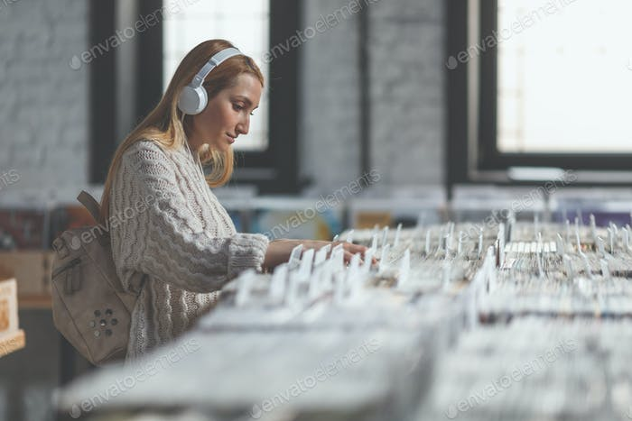 Attractive woman with headphones browsing records