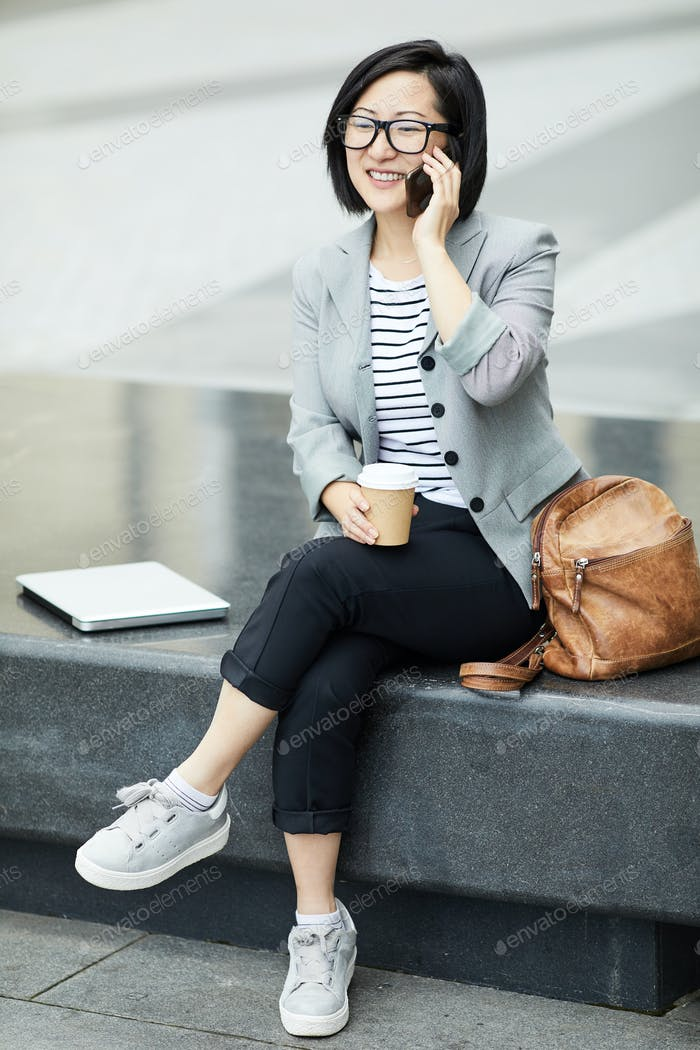 Asian Woman Speaking by Smartphone Outdoors