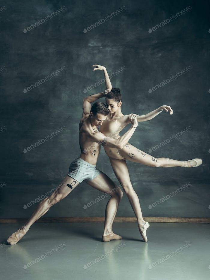 Los jóvenes bailarines de ballet Moderno posando sobre Fondo gris Estudio